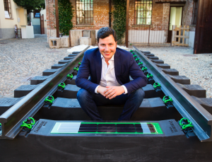 Greenrail CEO and founder Giovanni De Lisi sitting on a prototype of the sleepers obtained with recycled plastic and tyre rubber - Credits: Greenrail